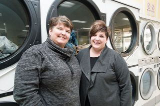 Marcus Larson/News-Register##Julie Roshak and Lisa Thoele operate Loads of Hope, a monthly ministry at the Newberg Coin Laundromat. The friends supply quarters to help low-income and homeless people wash clothes.