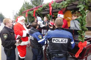 "Starla Pointer/News-Register##Carlton police officers and Santa stop a horse-drawn carriage Saturday in order to give youngsters stuffed animals and candy. The ""Santa Patrol"" is a Christmas tradition in Carlton, although this is the first time police have stopped a horse-drawn vehicle during the event."