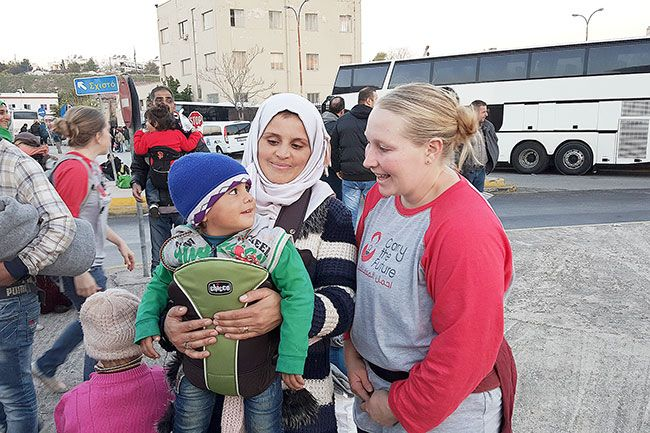 Submitted photo##Christine Anderson shares a smile with the toddler she just placed in a carrier. The McMinnville woman recently spent 10 days in Greece volunteering with the Carry the Future organization, which fits refugee parents with baby carriers to help ease their travels with young children.