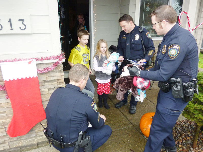 Starla Pointer / News-Register##Carlton officers, from left, Robert Anderson, Kevin Martinez and Jake Blair bring stuffed animals to the Nelson children, Conner, 11, and Sophia, 8, and their 3-year-old sister, Elayna (not pictured).