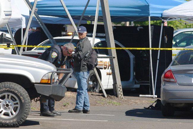 Rockne Roll/News-Register##A  Yamhill County Sheriff's Office patrol car is wedged under a transmission tower on the Christensen Auto Sales lot following Wednesday morning's fatal officer-involved shooting.