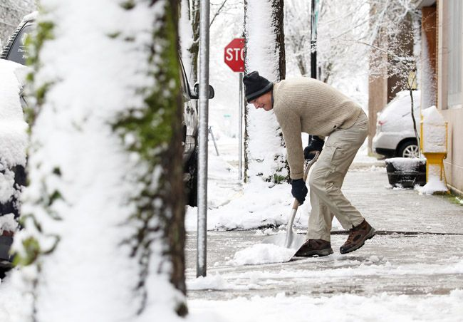 Rockne Roll/News-Register##Jim Affolter shovels snow from the sidewalk in front of his art gallery in McMinnville on Wednesday.