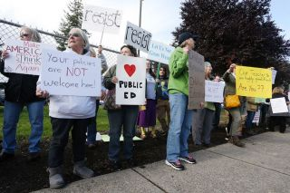 Rockne Roll / News-Register##Protesters stand on Evans Street across from McMinnville High School to protest U.S. Secretary of Education Betsy DeVos  visit to the school Wednesday afternoon.
