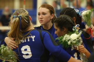 Rockne Roll/News-Register##Amity volleyball players Monica Eichler (9), Ani Keliiheleua (second from left) and Allie Steele (11) embrace in remembrance of the late Warriors assistant coach Tom Castor before Monday s Class 3A West Valley League contest against Santiam Christian.