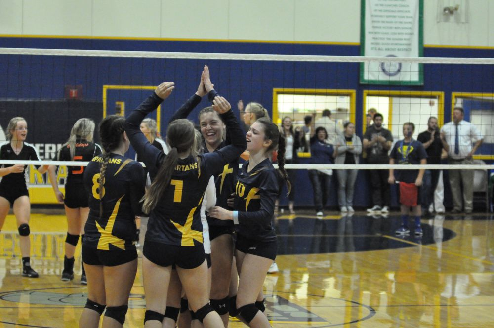 Robert Husseman/News-Register##The Sheridan Spartans celebrate their 16-25, 25-20, 25-22, 23-25, 15-8 victory over Willamina Thursday evening at Sheridan High School.