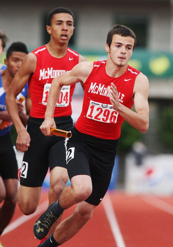 Rockne Roll/News-Register##McMinnville senior Brevin Geelan (right) takes off during the fourth and final leg of the 6A boys  4x400-meter relay Saturday as junior Will Payton looks on.