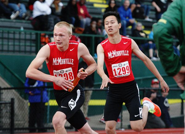 Rockne Roll/News-Register##Trustian Skeffington (left) receives the baton from Jerry Liu during McMinnville s performance in the 6A boys  4x400-meter relay Saturday.