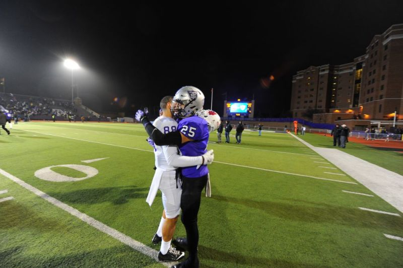 Courtesy of Rusty Rae##Linfield wide receiver Zach Kuzens (88) and St. Thomas defensive back Isaac Sheering embrace following Saturday s NCAA Division III semifinal contest.