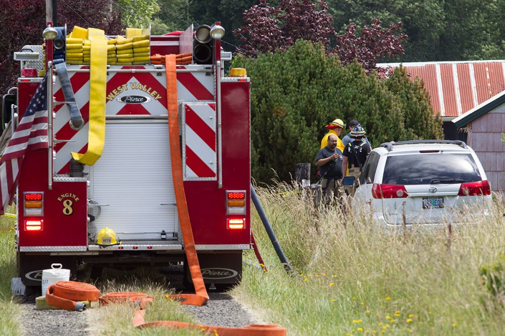 Rockne Roll/News-Register##Investigators work at the scene of an early Wednesday morning fire on Tenbush Lane in rural Willamina.