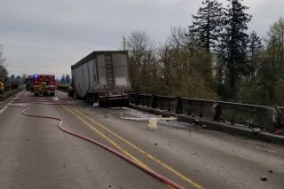 Submitted photo/Oregon State Police##Workers clean up fuel that spilled onto Highway 18, then into the Yamhill River at Dayton Monday following a truck crash.