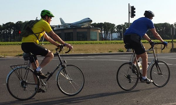 Dan Shryock/News-RegisterTwo Cycle Oregon riders pedal past Evergreen Air & Space Museum's water park early Sunday morning, July 13.
