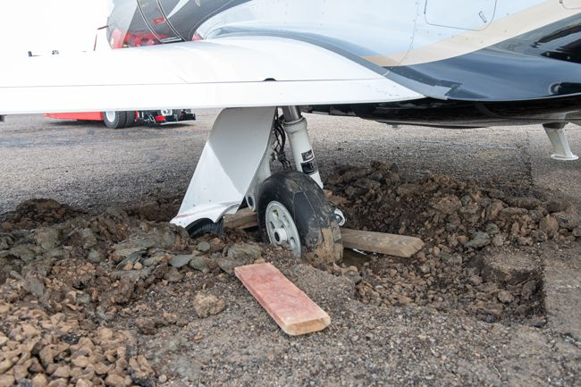 Rusty Rae / News-Register##The wheel of a busness  jet broke through old tarmac at the McMinnville Airport Friday.