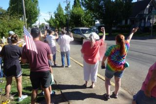 Starla Pointer / News-Register##Participants in an impromptu peace and diversity rally wave a passing traffic Friday morning.