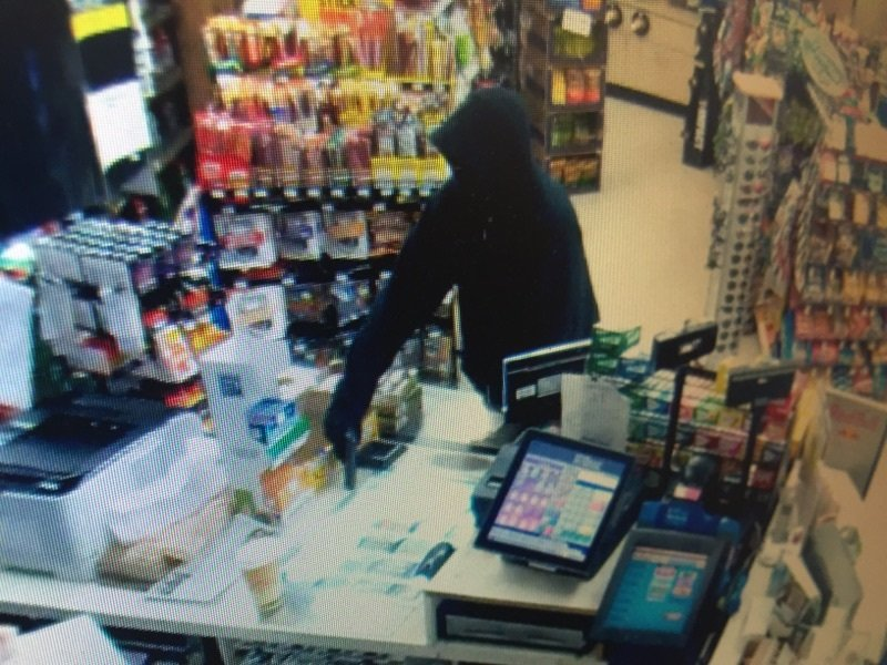 Submitted photos##Surveillance photo from the Plaid Pantry shows suspect at counter, threatening clerk with pistol.