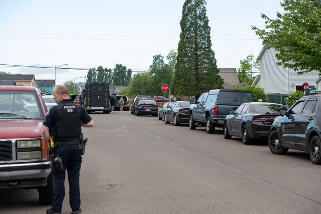 Rusty Rae/News-Register##A McMinnville Police Department K9 officer responds to Monday morning s standoff at a Northwest Evans Street residence in Sheridan as an Oregon State Police SWAT - Special Weapons and Tactical - vehicleis made ready for use.