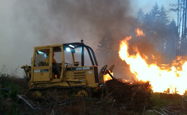 Photo by Don Everingham##Firefighters use a bulldozer to help clear combustable materials away from the flames.
